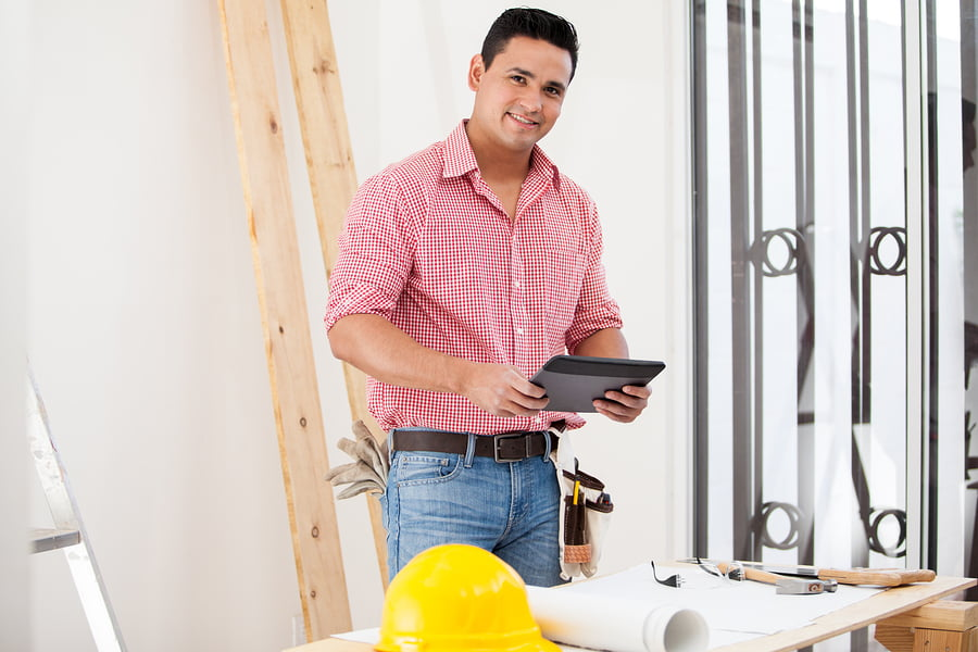 Happy Contractor Using A Tablet with Project Management Workflow Software