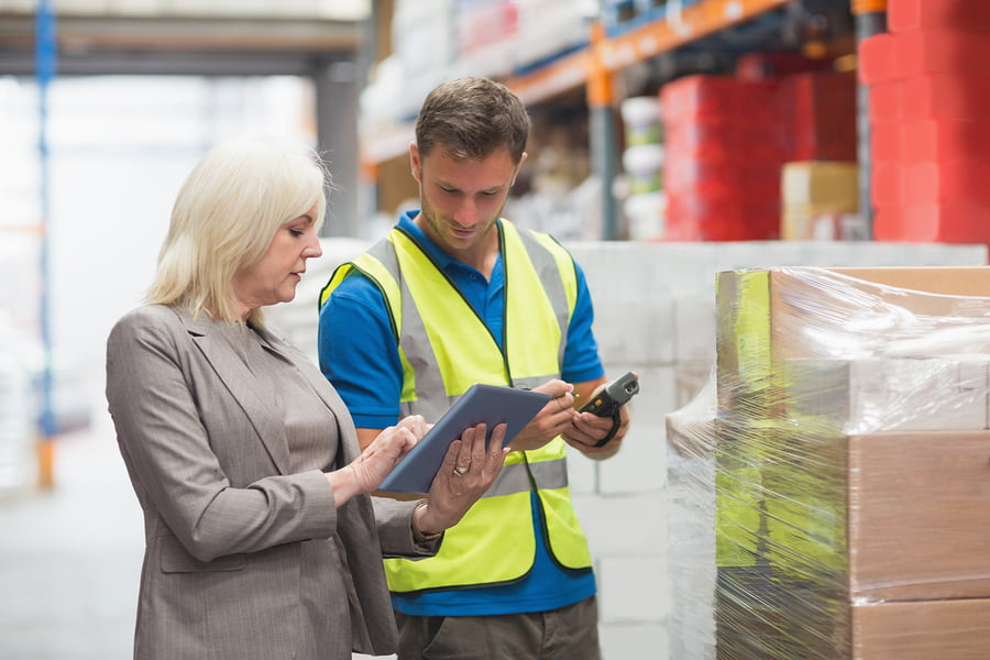 Manager using BPM solution on tablet while worker scanning package in warehouse
